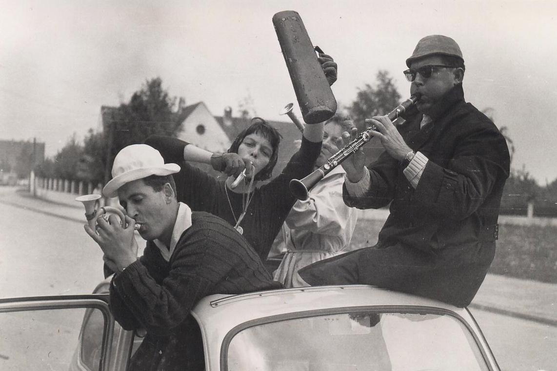 Freunde spielen Musik in einem Auto auf einer Straße in Bayern.