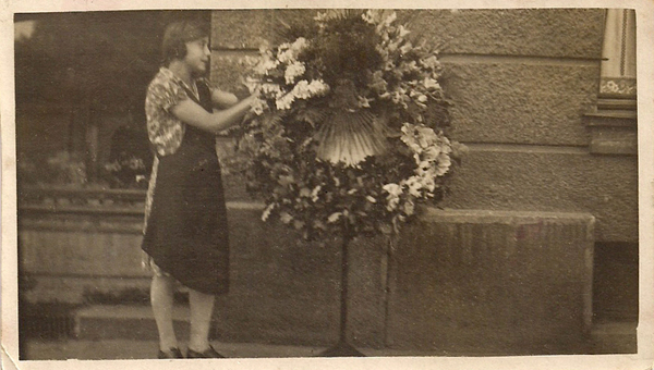 Auszubildende im Blumengeschäft von Johanna Schweiger am Ostfriedhof arrangiert Blumen an einem Kranz. ?Der Karl Valentin kam in dieser Zeit oft in unser Blumengeschäft an der Tegernseer Landstraße und seine erste Frage war dann: ?Wo is mei kleines Fräulein, des mia mein Hund zsammsitzt?? Dann ist die Leine unten an einem Hocker eingeklemmt worden, und ich hab mich draufsetzn müssn, damit der Hund, des war so a bissl a Stiagnglandamischung, nicht den Stuhl durch das ganze Geschäft gezogen hat. An seinem Halsband war ein kleins Tascherl ghängt und in dem ist ein Zettl dringsteckt: Ich heiße Fifi und gehöre dem Komiker Karl Valentin?. Der Valentin war groß und sehr mager, er hat immer ein bissl traurig und auch krank ausgschaut.? Und wenn?s ans Zahlen gegangen ist, dann hat er einen von seine Schuh auszogn und neben der Kasse abglegt??