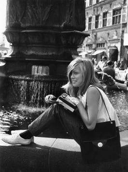 Jugendliche Schönheit genießt bei Musik den Sommertag an einem Brunnen in Kopenhagen.