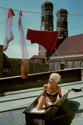 Eine junge, blonde Frau sitzt im Bikini in einer Badewanne auf einem Dach unter einer Wäscheleine mit trocknenden Nylonstrümpfen. Im Hintergrund ist die Frauenkirche in München zu sehen.